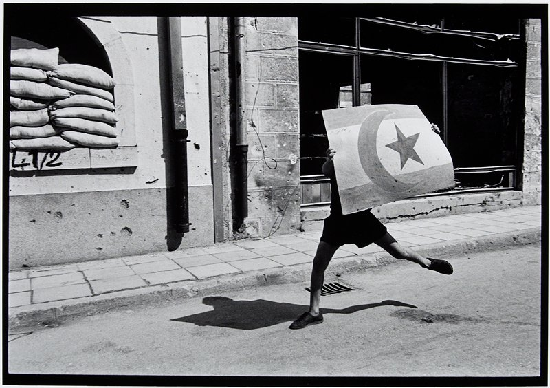 boy running with hand-made flag of cardboard