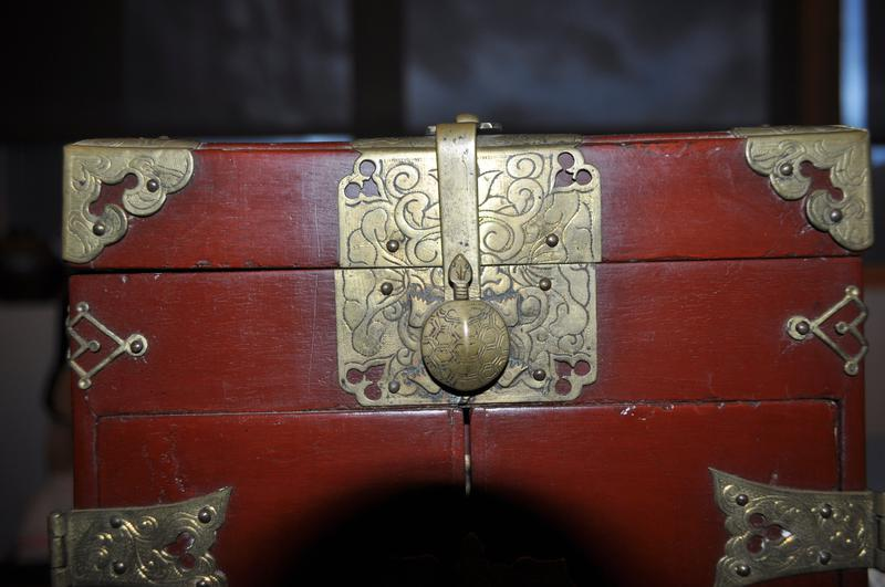 rectangular box with small feet with decorative openwork fittings and scrolling aprons; red exterior, black interior; turtle-shaped latch on front top; large openwork scalloped fitting on top front; decorative openwork fittings on top left and right edges and at top front; top cover hinged; pair of front doors open to reveal pair of drawers with round pulls