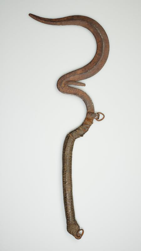long somewhat flat snake-like blade that includes three curves, a center ridge, and a handle on one end; a short-pointed prong extends from inside the center curve; the handle is wrapped in a fiber-like material; there is a loose ring attached to the end of the handle and one attached at the middle curve