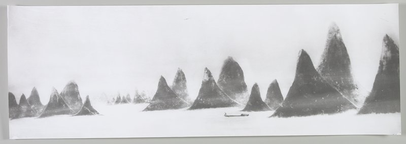 small figure rowing a boat R of center at bottom; pointed, dark land masses throughout; filmy atmosphere; Li River, Peoples Republic of China