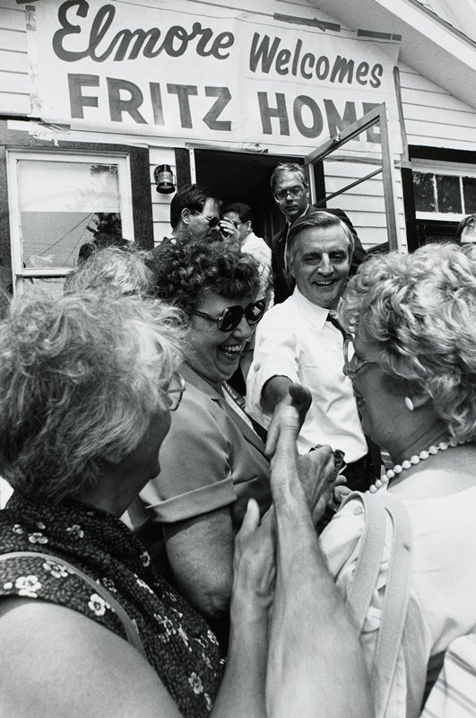 """Mondale shaking hands and surrounded by people, """"Elmore welcomes Fritz home"""" sign on building in background"""