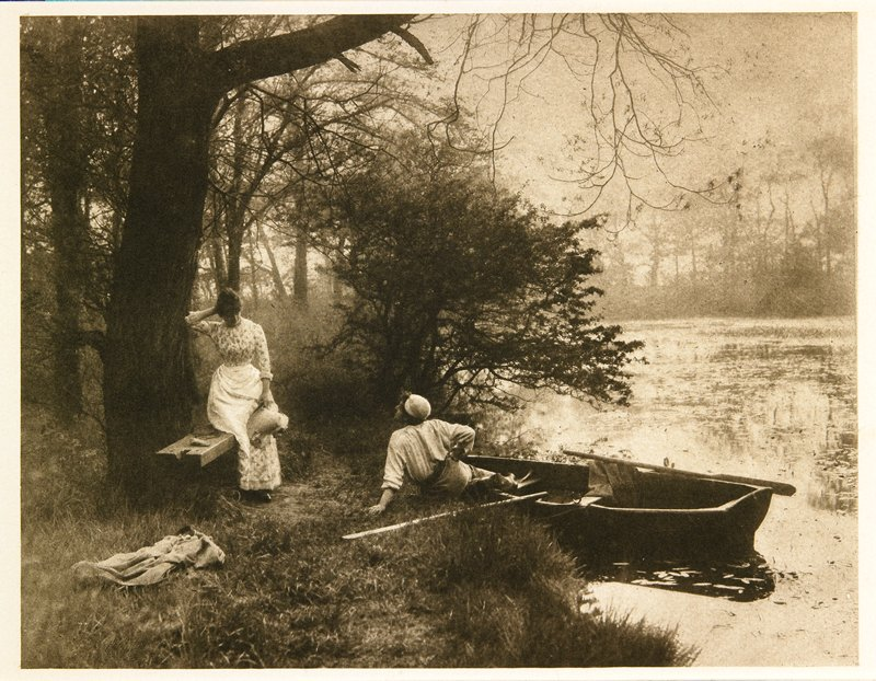 young man seated on a riverbank with his feet inside a small rowboat; man twists to look at young woman standing beside a bench; from a portfolio with essay on the photographer