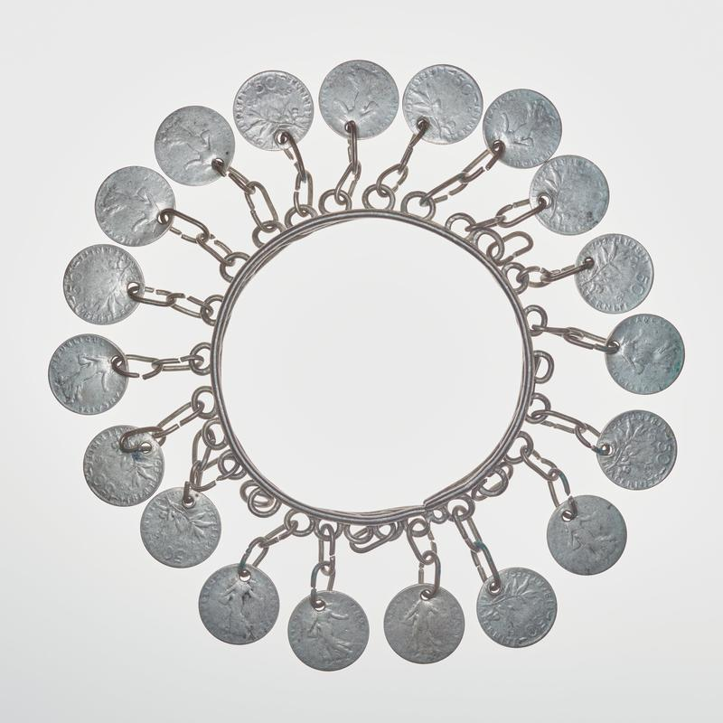 circular bangle with 19 coins, each attached by two oval chain links to a piece of twisted wire at middle of bracelet; coins are French 50 centimes pieces with a figure surrounded by text on one side and a branch of leaves with text on the other