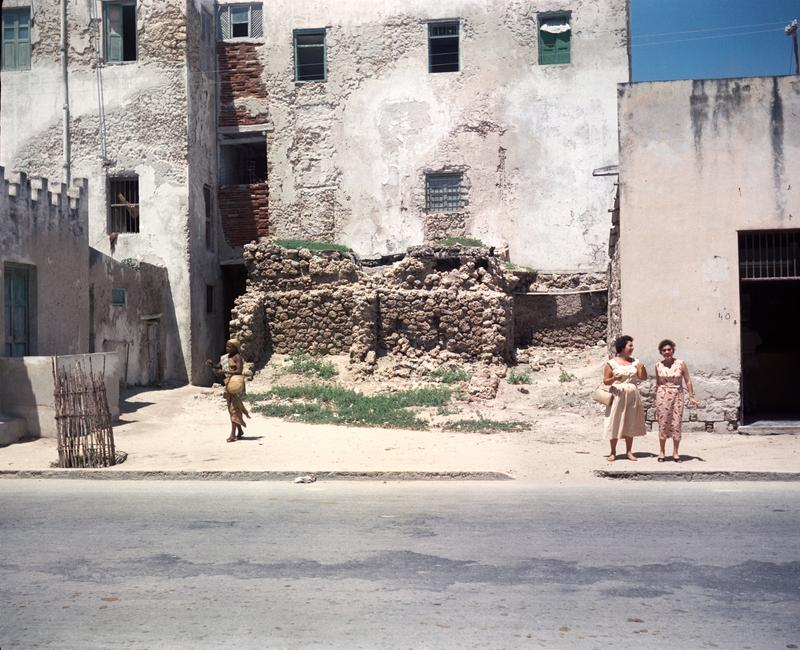 Color photograph of to women standing on the sidewalk to the right of a ruined building facade; a child walks to the left