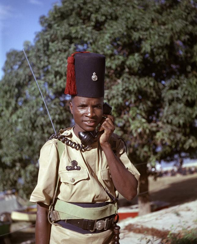 Color image of a portrait of a man in an army uniform wearing a fez-style hat and holding a telephone to his ear