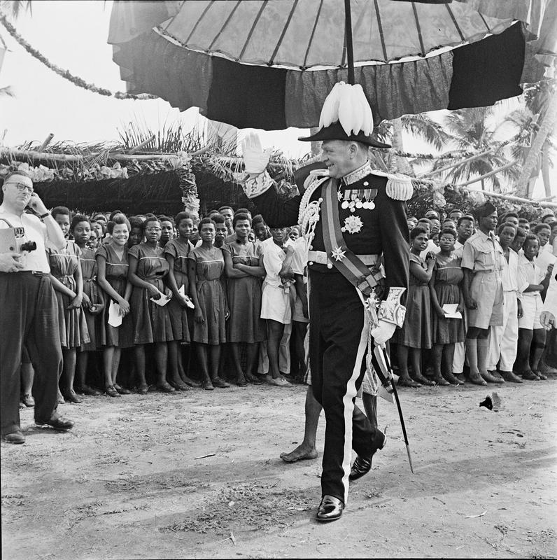 Black and white photo of a figure in the foreground wearing military regalia while walking under an umbrella with a crowd in the background looking on