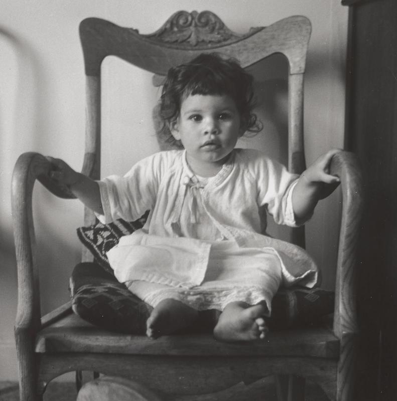 black and white image of a baby with dark hair seated in a wooden rocking chair