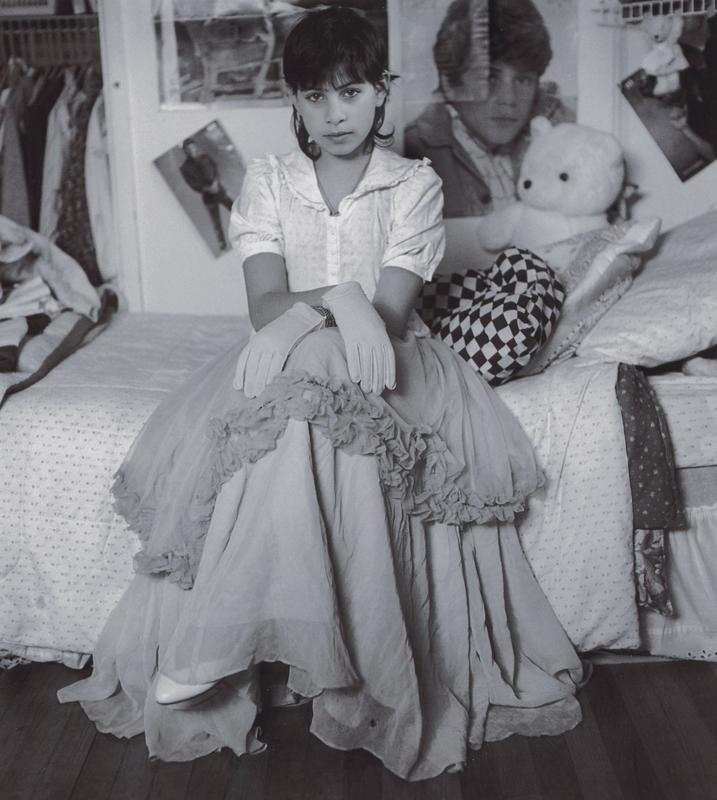 black and white image of a girl with short dark hair seated on a bed, wearing a short sleeved white blouse, gloves and a long skirt with a ruffle