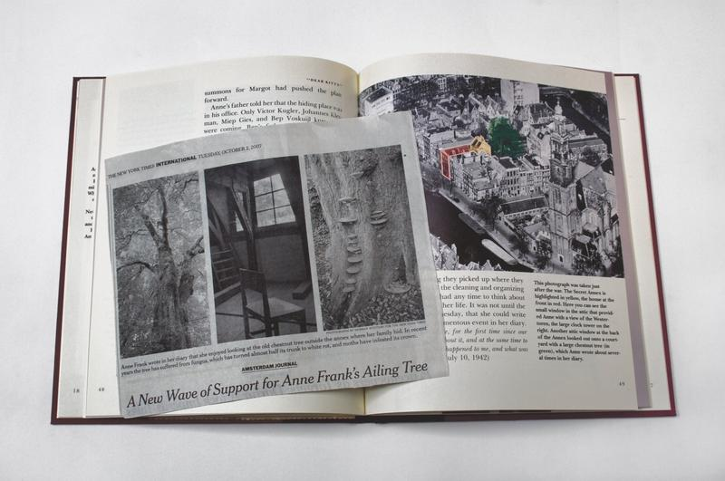 color image of a newspaper clipping with two pictures of trees flanking a picture of a sparce interior with one chair on top of an open book with an image of a highlighted building in a black and white photograph