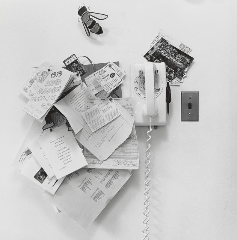 black and white image of a rotary dial wall telephone with postcards stuck beneath top right corner and light switch to right; small bulletin board with many pieces of paper (ticket stubs, invitations, receipts) to left of phone; bumble bee shaped wall ornament above bulletin board