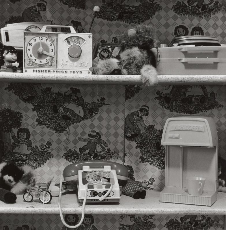 black and white image of toys including play telephone, play radio, play coffee maker, record player and tiny bicycle, on shelves with Raggedy Ann and Andy motifs on back