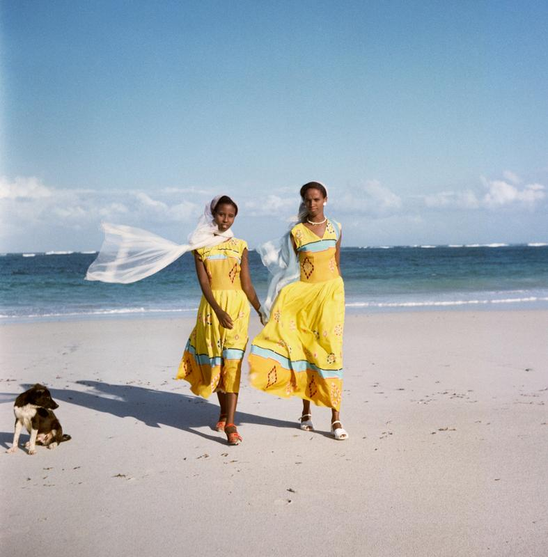 Color image of two girls wearing yellow dresses on a beach; a black and white dog in the LL corner