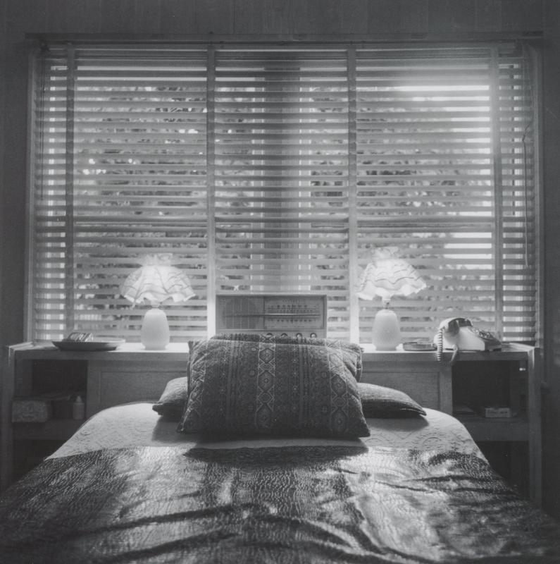 black and white image of a bedroom with a bed in foreground; pair of lamps with frilly shades, radio and telephone on a long dresser below a window with Venetian blinds