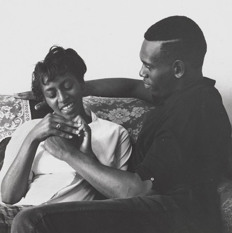 black and white image of a Black couple seated together, holding hands; woman holds man's PL hand in both of hers