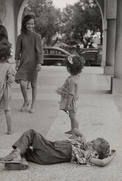 black and white image of children on a sidewalk; little boy wearing espadrille shoes and a plaid shirt lying in foreground; standing girl with curly hair wearing a visor behind boy; standing children at left