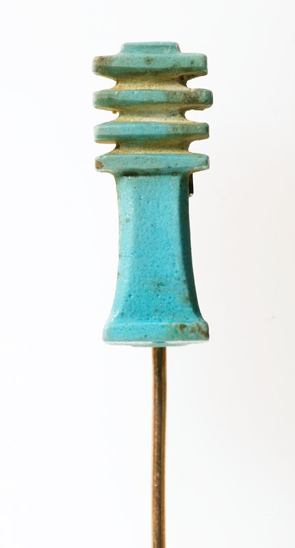 Pin, faience (brass), backbone of Osiris, symbol of stability, Egyptian, XXI Dynasty cat. card dims L. 1-1/16', W. 7/16' Djed; backbone of Osiris, symbol of stability; blue faience