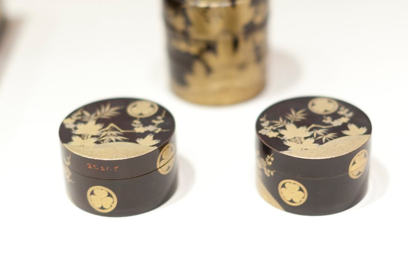 Round covered toilet box of black lacquer decorated with copper and gold in tree and floral notives; bearing three times the crest of the Tokugawa family, three asarum (ginger) leaves, their points together within a circle.