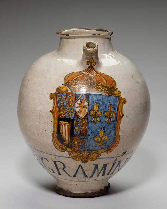 drug pot or pharmacy ewer with white glaze finish; decorated in colors with the arms of Charles I, King of England and his wife, Henrietta Marie, daughter of Henry IV of France and of Marie de Medici; moulded handle decorated with mask and small spout; below arms Latin name of drug 'Agraminis'