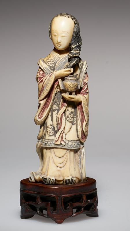 carved figure holding incense burner