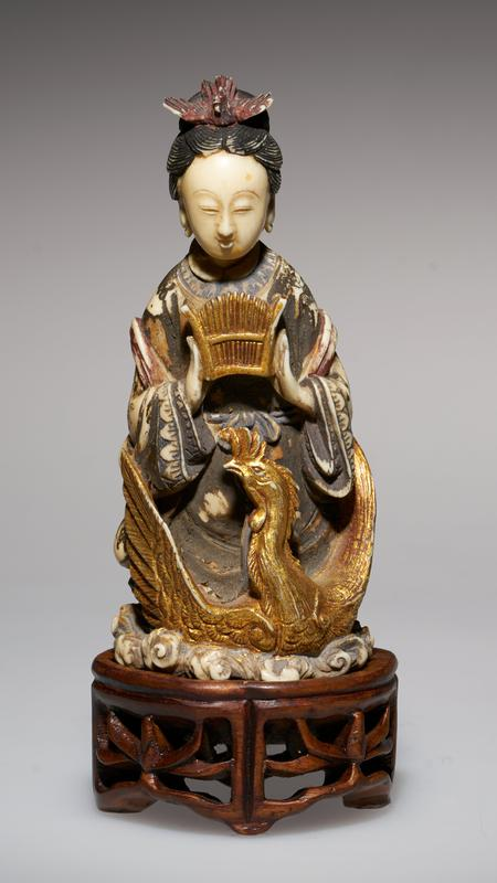 carved figure, holding a Symbol, seated on a Phoenix