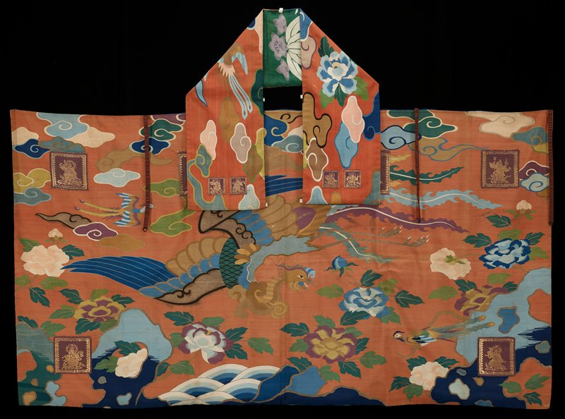 long band of silk tapestry known as tsuzure-ori, literally, 'patched weaving'; clouds, a flying bird and a large blue flower against a henna ground. Two small silk and gold tapestry squares set in each end; lined with silk painted with leaves and flowers on a green ground.