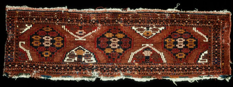 Camel bag, Bokhara. Deep red ground on which are three whole and four half octagons. A geometrical pattern on a red ground serves for a border stripe. Sides originally finished with a single cord, and ends with a selvedge turned under. At one end a red and blue fringe has been sewed. Senna knot.