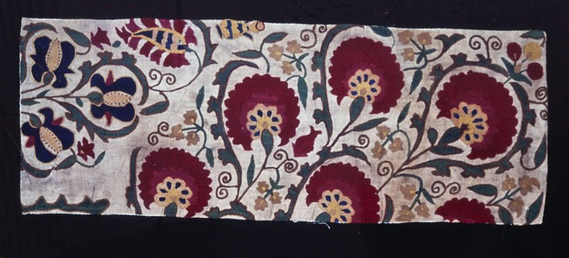 Piece of tan linen embroidered with leafy scrolls and large red flowers. Fragment of much larger piece, Lined with unbleached muslin. Linen