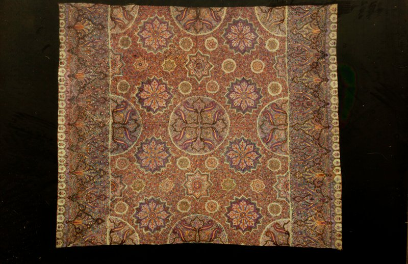 Piece of tan material thickly embrodered - the borders at either side with patterns similar to shawl patterns, and the center with medallions of various sizes surrounded by an all-over floral vine pattern. Probably part of a larger piece. Cotton, embroidered.