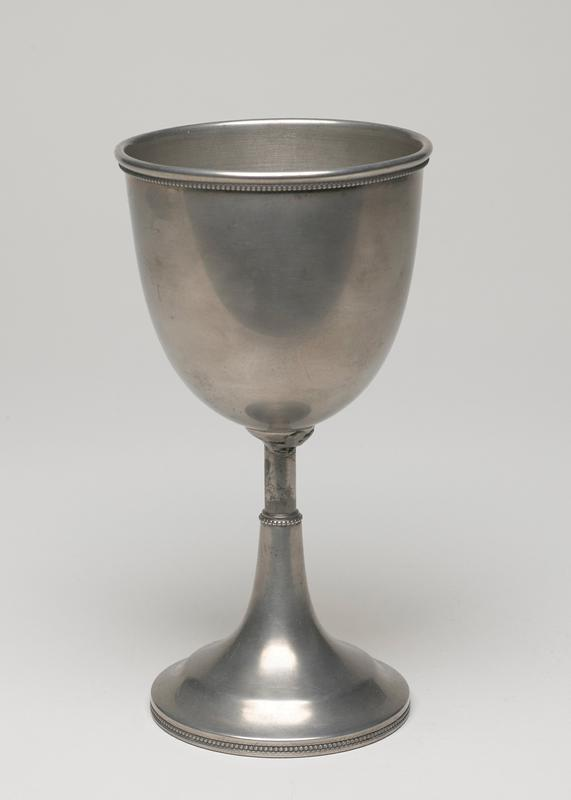 Goblet, white metal, cat. card dims H 7-1/4 x D 3-3/4' thin stem and round base, beaded around base, center stem and rim, shows the influence of the silversmiths of the period.