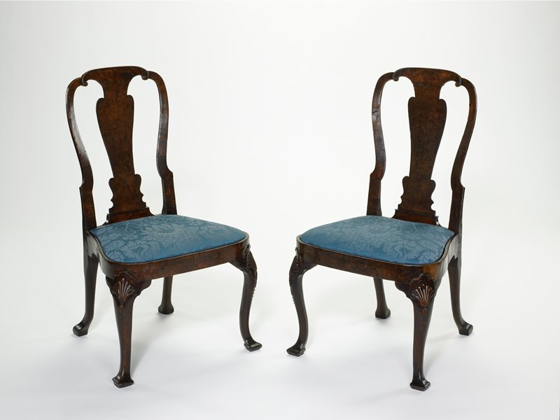 Side Chairs, pair of, with hoop backs and shaped splats; attenuated cabriole legs in front, end in spatulate feet. The knees are carved with a shell motif. Slip seats upholstered in blue and silver brocade.