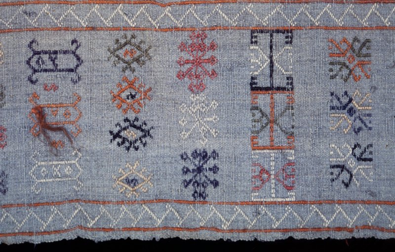 Tent Hanging, embroidered; composed of four strips of burlap-like material in alternating colors - red, pale blue, yellow, darker blue all of which are embroidered with geometric designs. There are several long pieces of wool or hair knotted into the warp threads - to ward off the evil eye. Wool