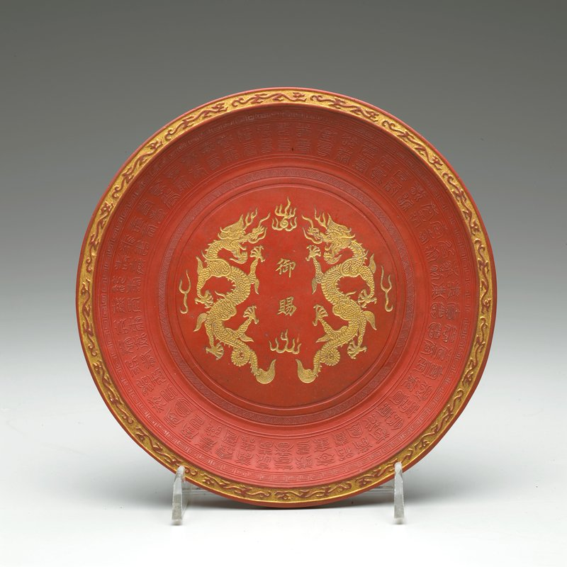 dish-shaped red ink cake with incised gilt dragons and 2 gilt characters at center; gilt inscription inside square on bottom; 2 rows of raised characters around edge; raised abstracted dragons around edge on bottom