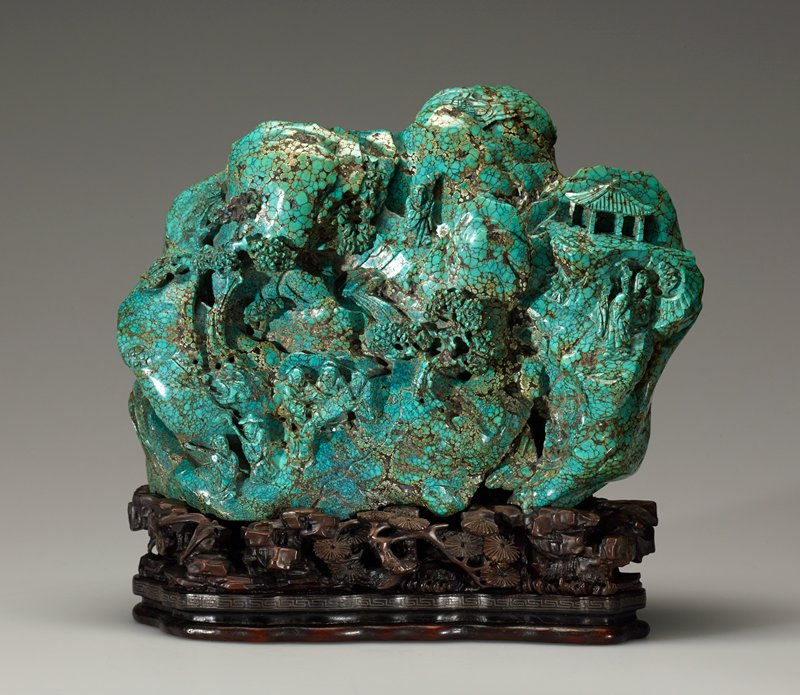Turquoise carving in the form of a mountain; design of figures, flowers and shrubs.