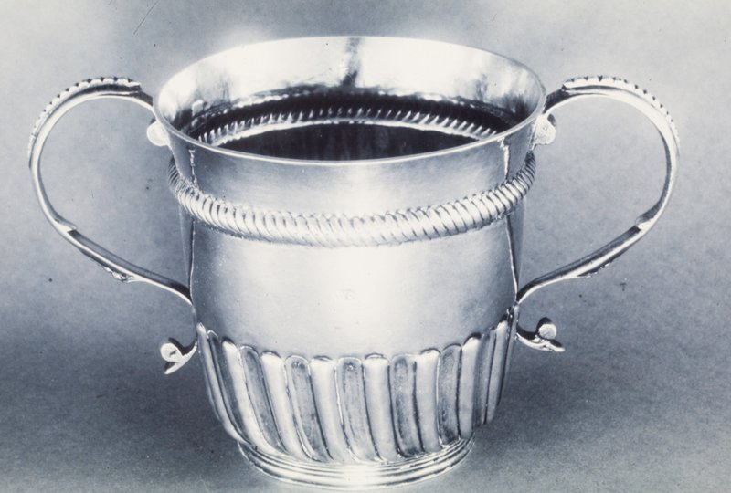 two-handled cup, lower parts of the body decorated with bands of spiral, twisting fluting over a shallow reeded foot; slightly flaring rim above a narrow band of gadrooning; scrolled handles decorated with beading