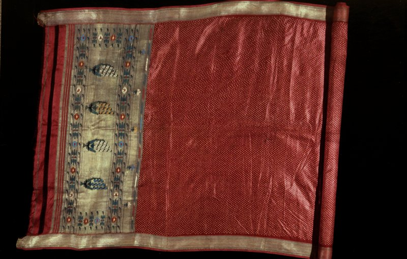 Sari, red foulard ground covered with small white tied and dyed circles. Wide red and gold border sewed on at sides, and deep border sewed on at one end. This border carries geometrical designs and formalized trees in green, blue, cream, peach and red, all on a gold ground. Border at one end only. Both ends unfinished. One end of red foulard lined with thin red cotton printed with herringbone design in yellow.