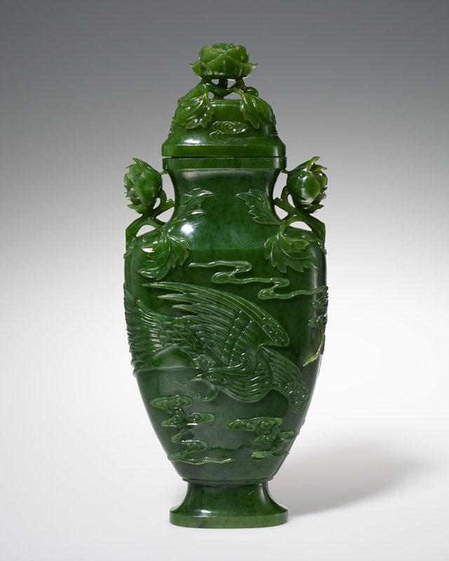 Vase, emerald green spinach jade, with cover. On each side of the body a phoenix in flight surrounded by cloud forms and trailing streamers in relief. Handles and finial of bold peony buds deeply undercut.