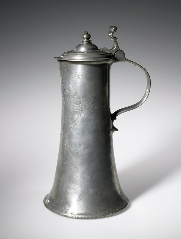 flagon, tapered cylindrical body with dished lid, slightly domed in center to carry lid-peg, handle with bold outward sweep meets body less than half way down, a characteristic or early German flagons, erect thumbpiece, on front of body an engraved shield with scrolled mantlings bearing initials [H.A.M.S.] and date