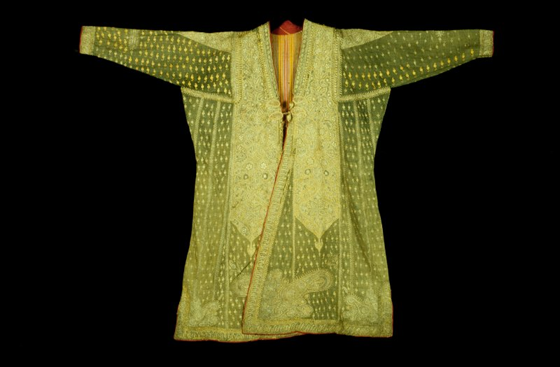 Green wool coat embroidered in silver and gold. Body of coat made of gored sections with an all-over design of single blossoms embroidered in gold. On either side of front opening a shaped panel solidly embroidered in a design of stylized floral sprays and arabesque. A large panel of same design covers three quarters of back of coat. Opening and bottom edged with a narrow n\band embroidered with pear forms and blossoms, and bottom\m corners, font and back, with large flower-filled pears. Dolman sleeves with embroidered epaulet sections. Lining of colored, striped cotton.