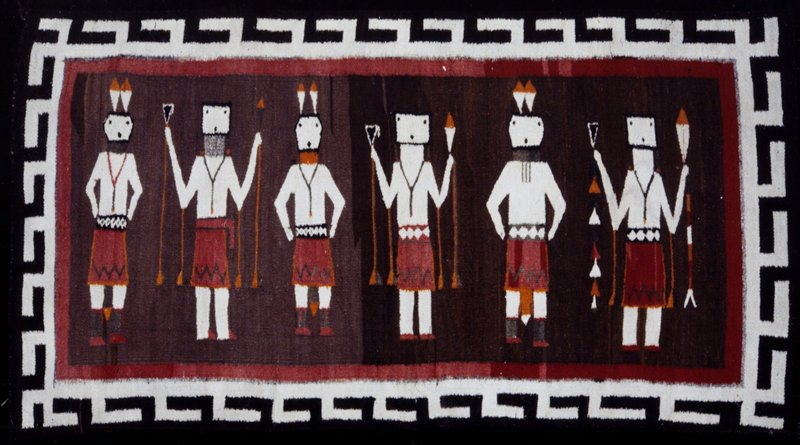 """rug, so-called """"Sand Painting""""; tan field, bordered in rose, with six human figures in attitudes of a ceremonial dance; border of hook design in dark brown on white; rug shows human dancers wearing Yei masks for ceremonial performance; rug is termed a Yeibichai"""
