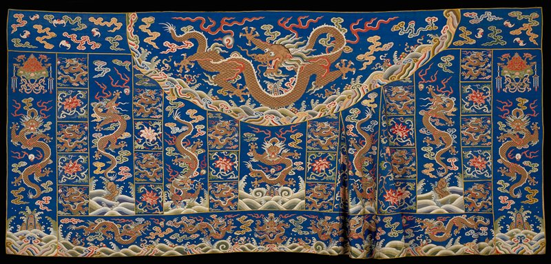 Buddhist priest robe, kesi, Kangxi blue. An exceptionally fine example of kesi weaving with five-clawed dragons in gold and individual flower motifs in shades of red and pink. Patched character of robe achieved with narrow bindings of yellow satin.