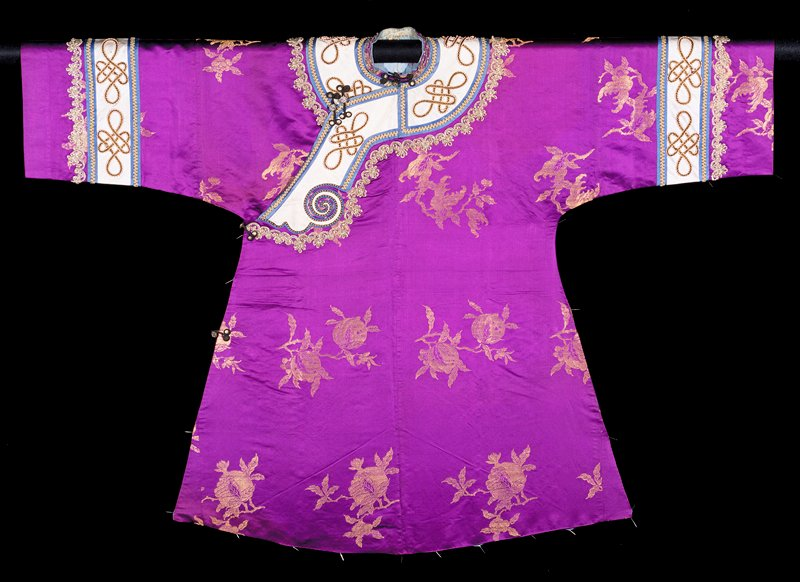 Robe of violet satin brocaded in gold with widely spaced double-peach and pomegranate. Wide sleeves banded with light blue satin with braid applique above a beaded swag. Collar band of same. These bands, Victorian in flavor, much later than the brocade of the robe proper. Robe slit at sides and lined with thin blue silk. Note pocket on under side of front.