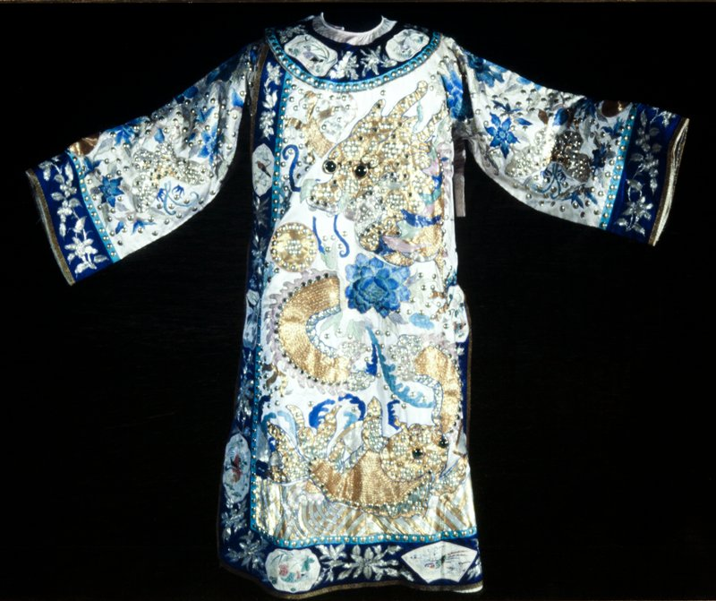 Theatrical robe of palest lavendar satin with couched and embroidered applique designs in gold, silver, green, and peacock blue silk threads. In the field two large gold four-clawed gold dragons with bulging green glass eyes and studded with mirror and metal studs. Below dragons, front and back, two gold fish in same technique. On sleeves silver thread butterflies and gold thread frogs, also with studs and green glass eyes. Surrounding these animals in the field are embroidered applique peonies and single clouds. Cuffs, collar-band and border of bright blue satin with appliqued flowers of couched silver threads, and shaped, embroidered applique medallions of white satin. Large silvered studs scattered liberally over ground and along all borders. Lining of coarse linen. Robe boned under arms and fitted with deep satin loops- for a belt? Inscription inside front.