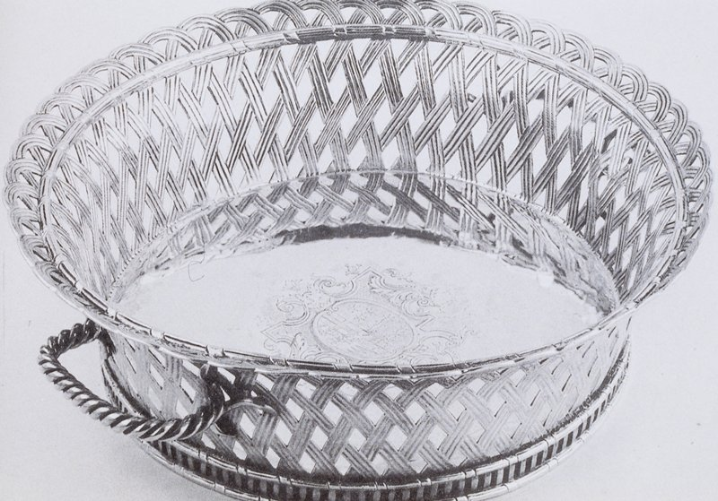 A superb round, flared, scalloped rim basket with sides of three strand open basket weave; low pierced rim foot; two rope work handles. Center engraved with coat of arms, crest, ribbon and motto within strapwork and foliate cartouches on hatched ground flanked by caryatid supporters and leering masks below. Arms: of George Baillie of Jerviswood and Mellerstain, and his wife, Grisell, whom he married in 1690, 5th daughter of Sir Patrick Hume, later (1697) 1st Earl of Marchmont. He had, like his father-in-law, been an exile in Holland, his father having been executed for alleded complicity in the Rye House plot. Motto: Maior Wirtus Quam Splendor - Virtue is Greater than Splendour.