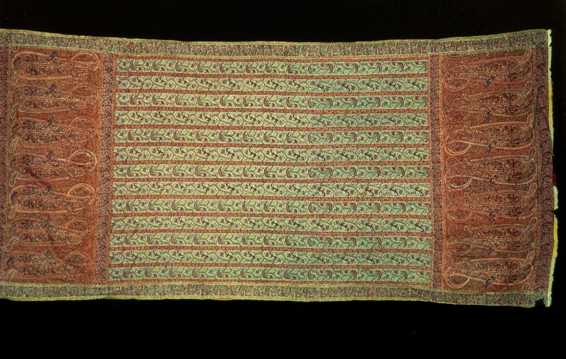 Doshalla, or long shawl, hand-loom woven, made of jamawar, a patterned shawl cloth woven by the yard, and finished with separate woven borders. Design of alternating vertical stripes. The wide one carrying a running floral design in which pinks are the chief blossom, the narrow one a reciprocal floral band. Pale blue ground. Wide end borders with a band of large cones. Black cotton lining. # 8.