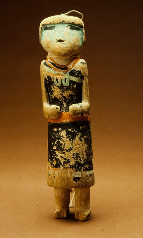 Hopi ceremonial doll, painted; face blue, head black, with top-knot of feathers; black sleeveless robe decorated with necklace and bands of blue and orange; twentieth century