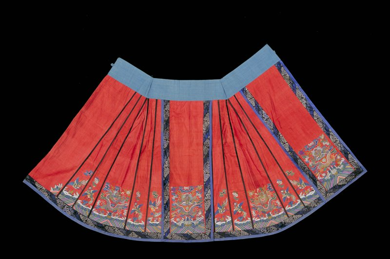 Skirt of red k'ossu weave, the side sections gored, bound with black satin, and decorated in the lower area with phoenix, cloud, and Eternal Sea motif in shades of blue, green, yellow, apricot, mauve, and pink. Main panels have a seated five-clawed dragon in gold thread; bats, clouds, Buddhist symbols, and Eternal Sea in the same colors used in side sections. Main panels and bottom bordered with a band of black satin embroidered with Buddhist symbols in shades of blue and edged iwth band of medium blue satin. Lining of faded pink diapered silk.