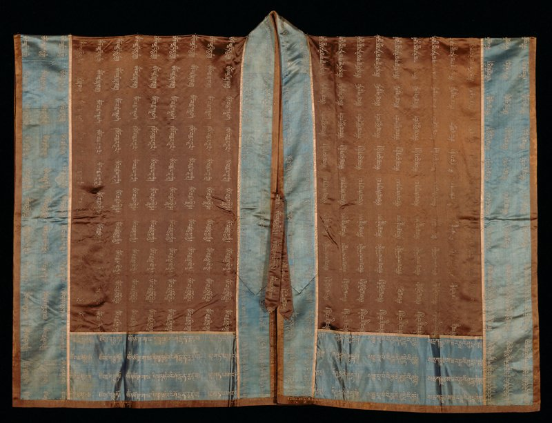 Priest robe of embroidered and brocaded puce satin. The shape of the robe is Taoist and the satin is brocaded in an all-over design in spaced, vertical lines, with running Sanskrit characters (prayers) in gold thread. Over this ground on back are enbroidered in laid couched work figures of the 18 Lohans. Colors of embroidery (later work ?) include blues, yellow, rose, peach, green, black, ivory and tan. On left shoulder blade a pagoda; on right, a dragon. Around bottom, sides and front a border of soft blue satin brocaded with the body characters in silver threads. This border banded, on outer edge, with a narrow strip of the puce brocade and set off from main body of robe with a narrow binding of pale beige satin with reveals brocaded areas. Two shaded strips of puce brocade attached to front for fastening. Lining of alternating strips of yellow and orange damask. Facing of plain puce satin around collar and down front; of brown silk damask around bottom and sides. A.P. thinks this may be one of 1738 Kuo Ch'in Wang tomb lot( Yun Li, 17th son of K'ang Hsi, died 1738)
