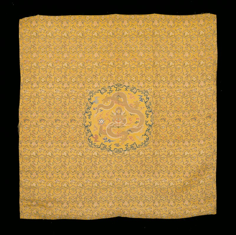 Throne cover of imperial yellow brocaded silk. Diaper ground six-petalled medallions and elongated hexagons in gold and blue, each containing a floral spray of a precious symbol. Central medallion edged with running border of loose clouds contains a five-clawed dragon in gold on plain ground. Colors include shades of blue, green, pink, mauve and rust-red. Lining of yellow damask with cloud design.