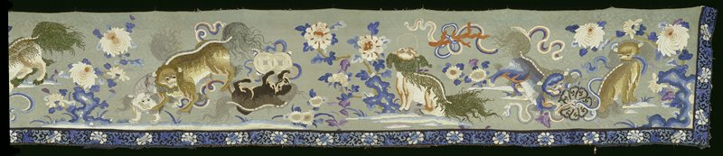 Valance of faded celadon figured silk, large sprays of lotus and wine foo dogs in shades of blue, cream, tan, pink,grey, rust, green and black. The manes and tails of some of the dogs embroidered with silk threads which have been wound with peacock feathers. Chiefly satin and couched stitch, but some areas in knot stitch. Lower and end borders of black satin embroidered with running peony design in shades of blue and white. Border frayed at edges. No lining.