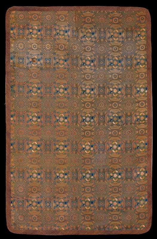 Rare temple hanging of leaf green brocade. All-over pattern composed of various square, octagon, and trefoil bordered medallions, each beating floral sprays or stylized blossoms. The medallions all carry floral or diapered borders, producing an effect of great richness and intricacy. The color is chiefly green, with shades of red, blue, yellow and pink contributing a lightness to the scheme. Border of gold and blue brocade of interlocking 'Y' design. The piece is made up of two widths sewed together, and is limed with a fine eggshell silk with wild goose medallions in openwork. Medallions also carry two characters of rather archaic flavor.